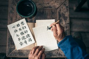 chinese senior man writing chinese calligraphy characters on paper