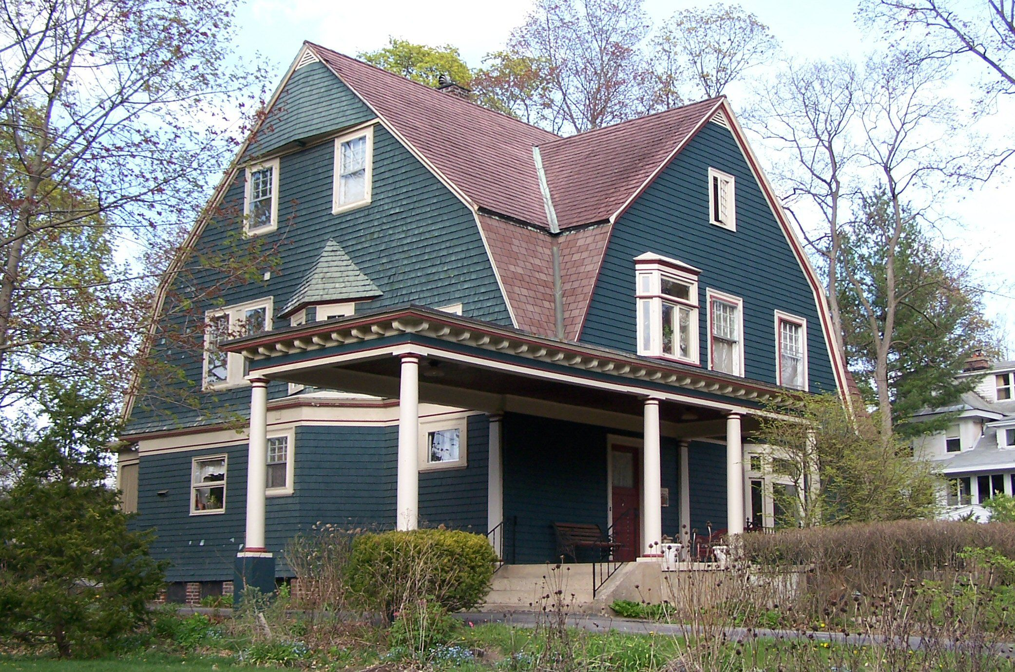 large, green shingled home, 2 1/2 stories, brown shingled cross-gambrel roof, front porch extends into a car port
