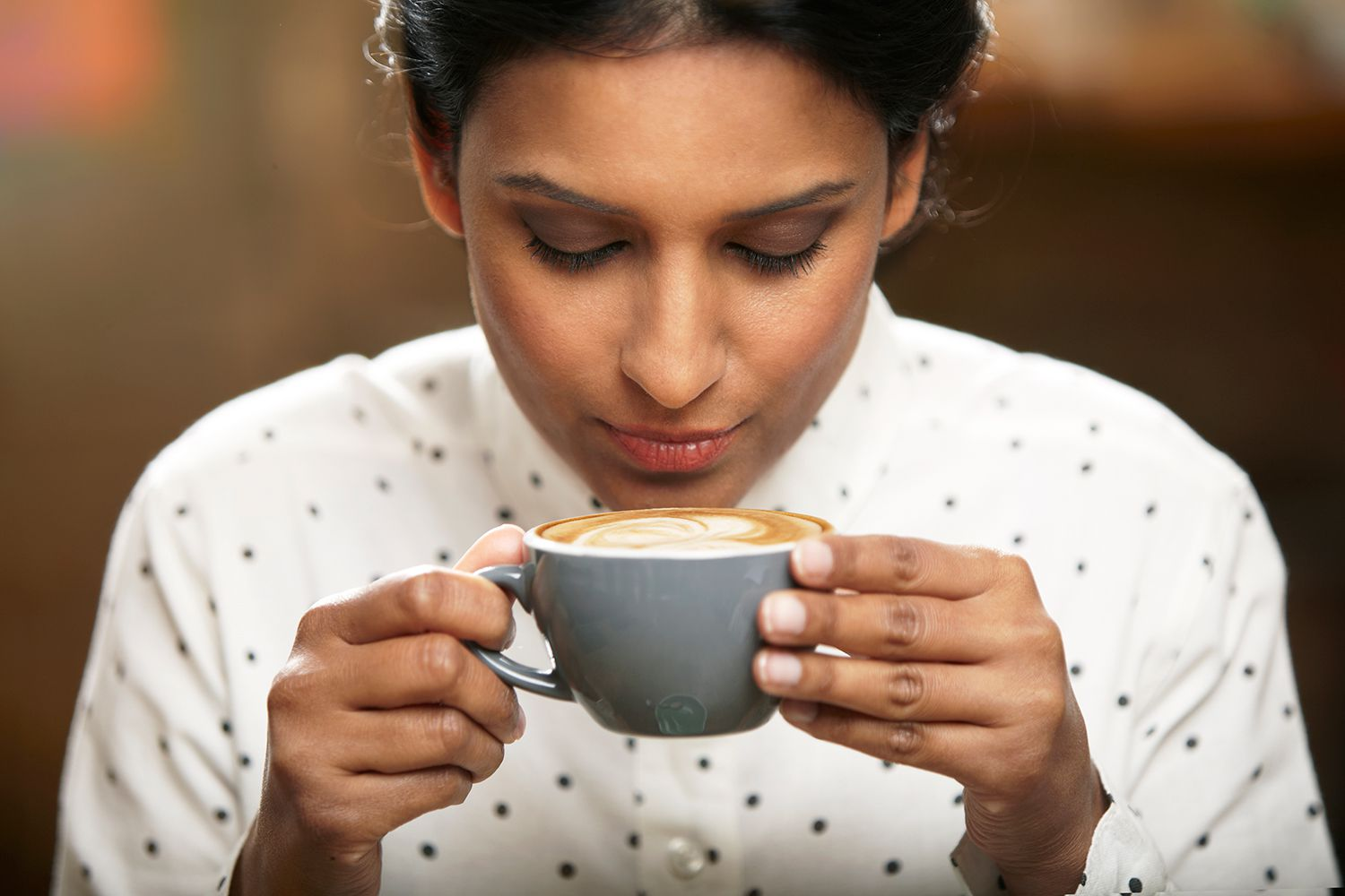 Woman about to drink a cup of coffee.