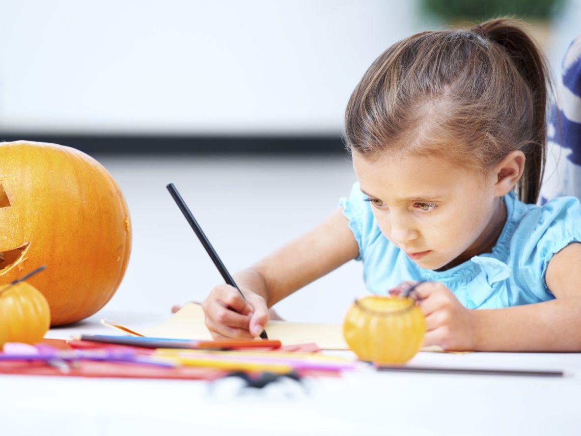 ジャック・オー・ランと一緒にテーブルで書いている女の子  彼女の横にあるランタン..