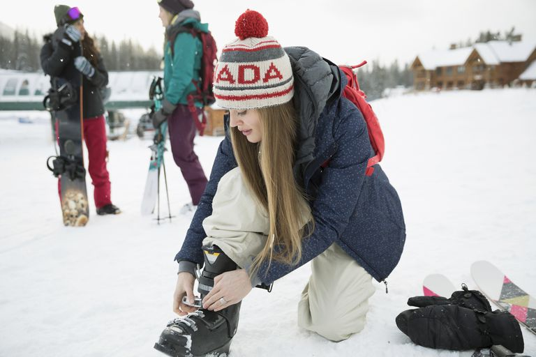Female snowboarder preparing ski boots, snowboarding with friends at ski resort