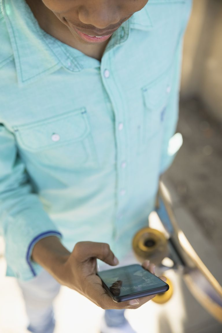 Young man with skateboard texting with smart phone