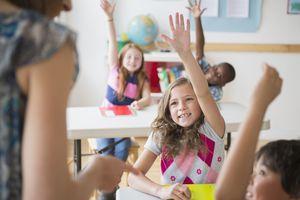 Children (8-9) raising hands in homeschool co-op