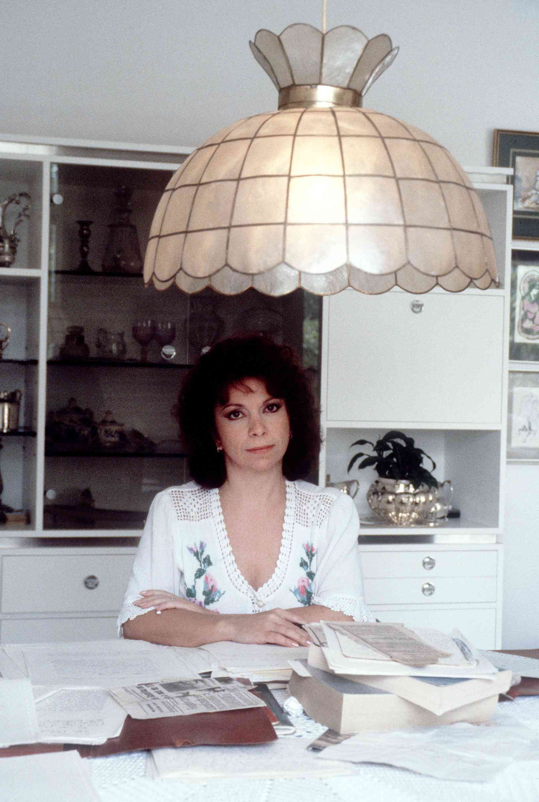 Isabel Allende at a desk covered in papers
