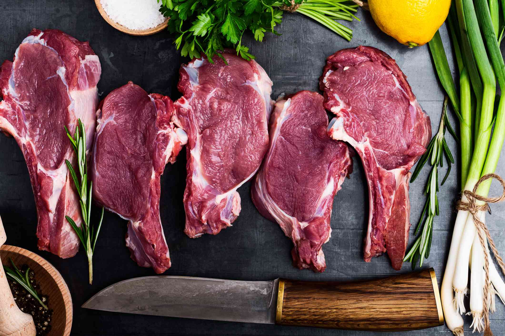 raw cuts of steak surrounded by herbs and a knife