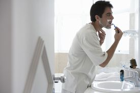 man shaving face in bathroom mirror