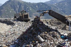 Machinery dumping waste in landfill