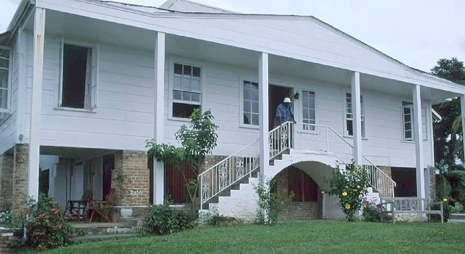 raised ranch with added pediment and six posts, double stairway to second level front door