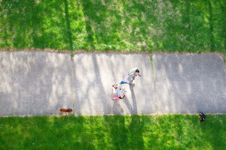 Above view of people walking along a sidewalk.