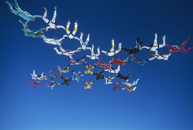 Skydivers holding hands in net formation in blue sky