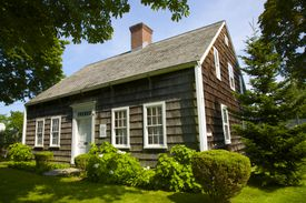 Brown-shingled, center chimney, 6-over-6 double hung windows on each side of central doorway, Cape Cod style house on Long Island, New York