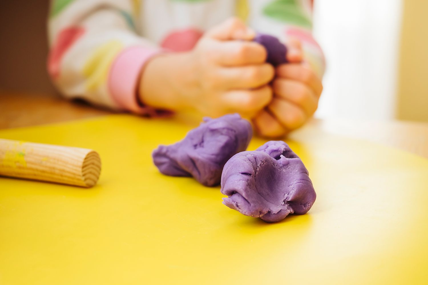Childs hands kneading modelling clay