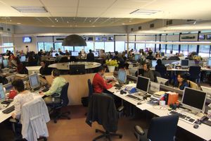 Active newsroom filled with people and equipment.