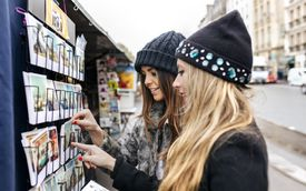 Two friends looking for postcards in Paris