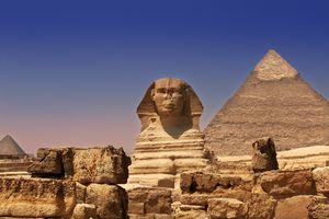Pyramid and Sphinx in Egypt under a blue sky.