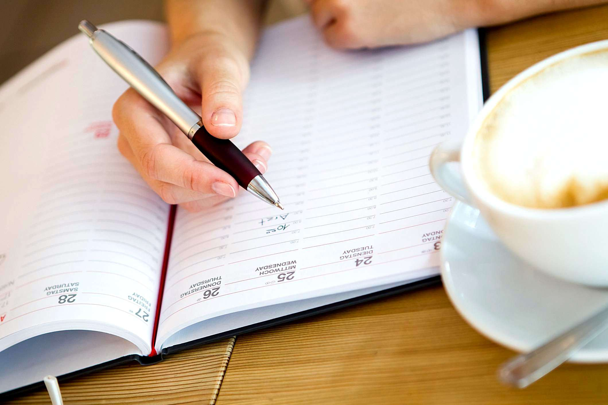 Hands writing in a planner at a local coffee shop