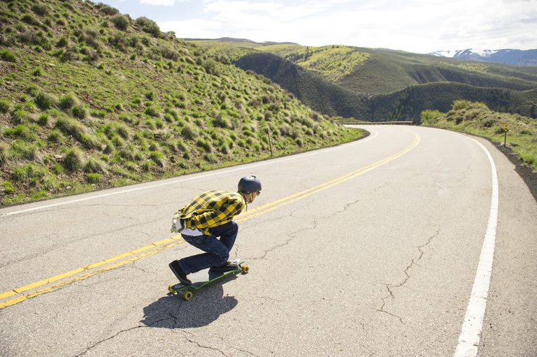Behind view of long boarder on mountain road