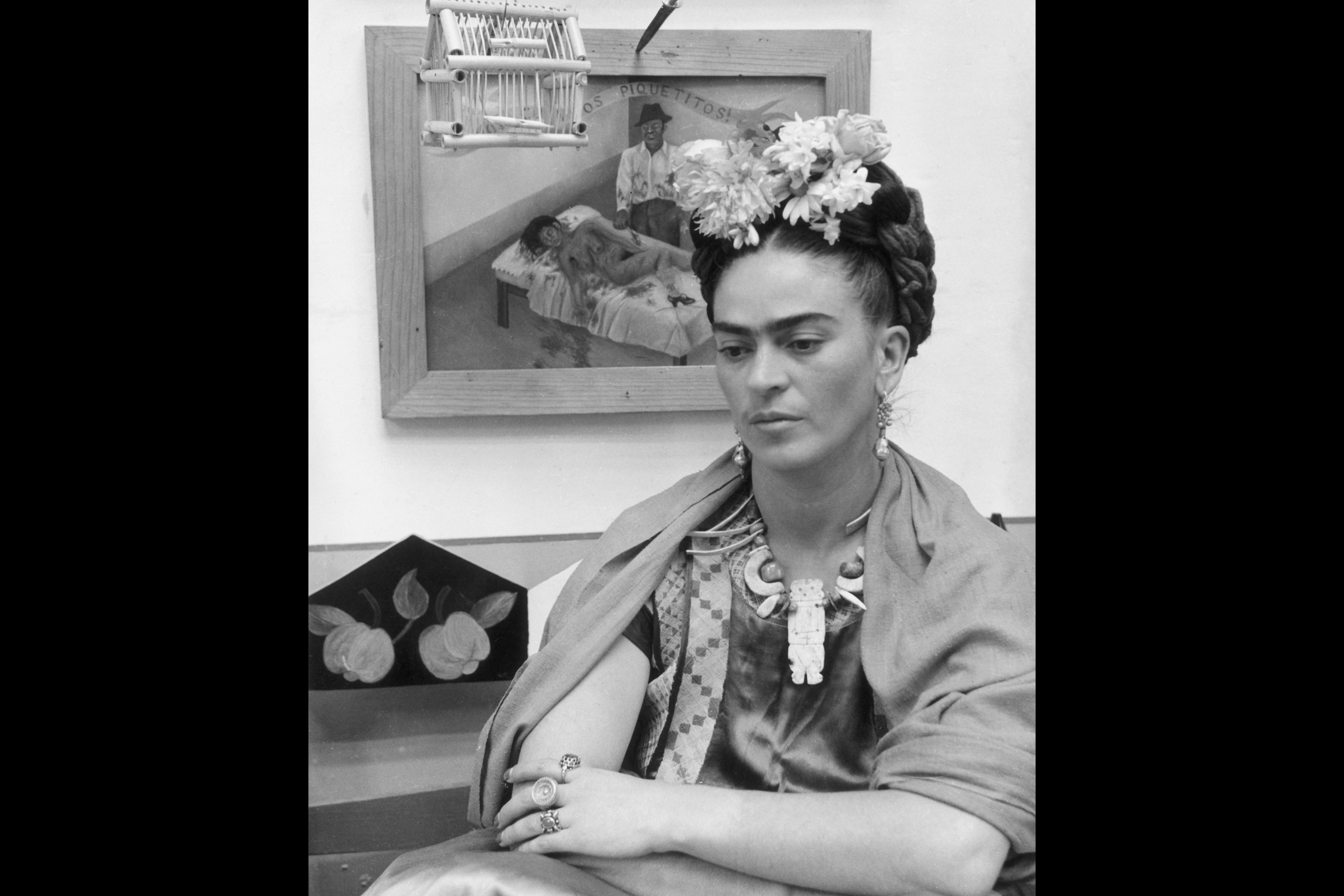Mexican painter Frida Kahlo sits with her arms folded, looking down, in front of one of her paintings and a wooden bird cage.