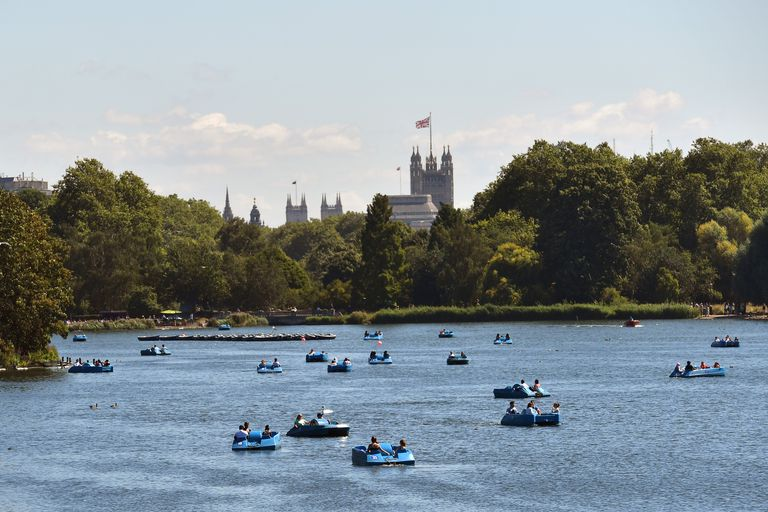 People relax on boats on the Serpentine lake in London, England