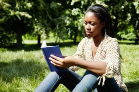 woman reads a blue book on the grass