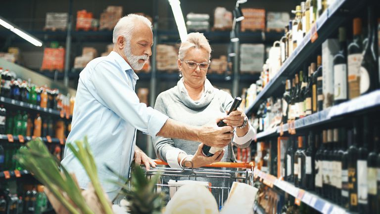 A middle-aged couple chooses a bottle of wine from a grocery store.