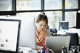 Woman sitting at desk working on laptop writing Java conditional statements