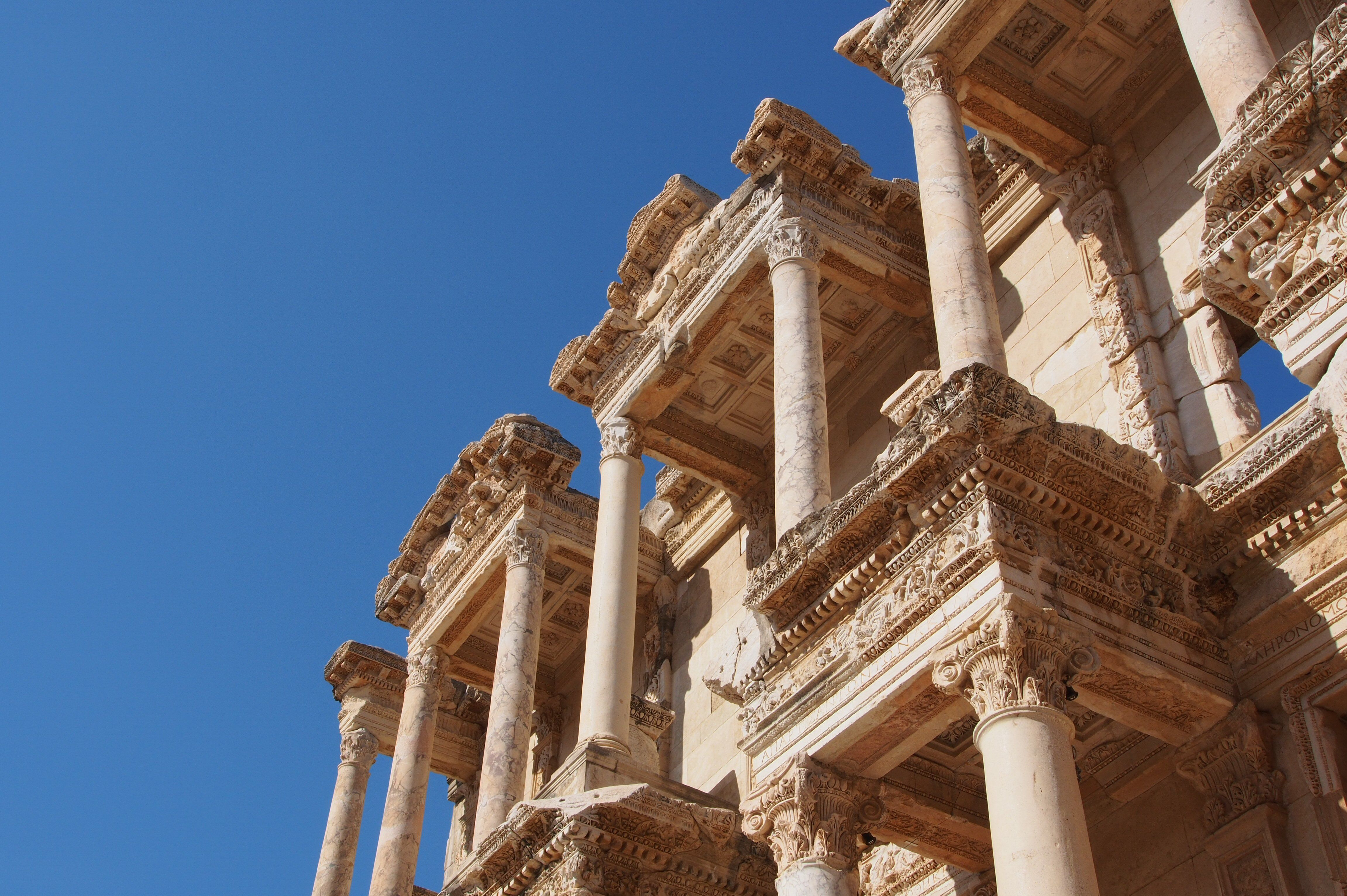 Low angle looking up the ruined facade of the columns and pediments of the Celsus Library in Ephesus, Turkey