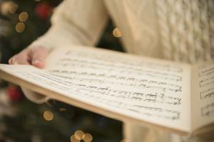 Studio Shot of woman holding sheet music at christmas