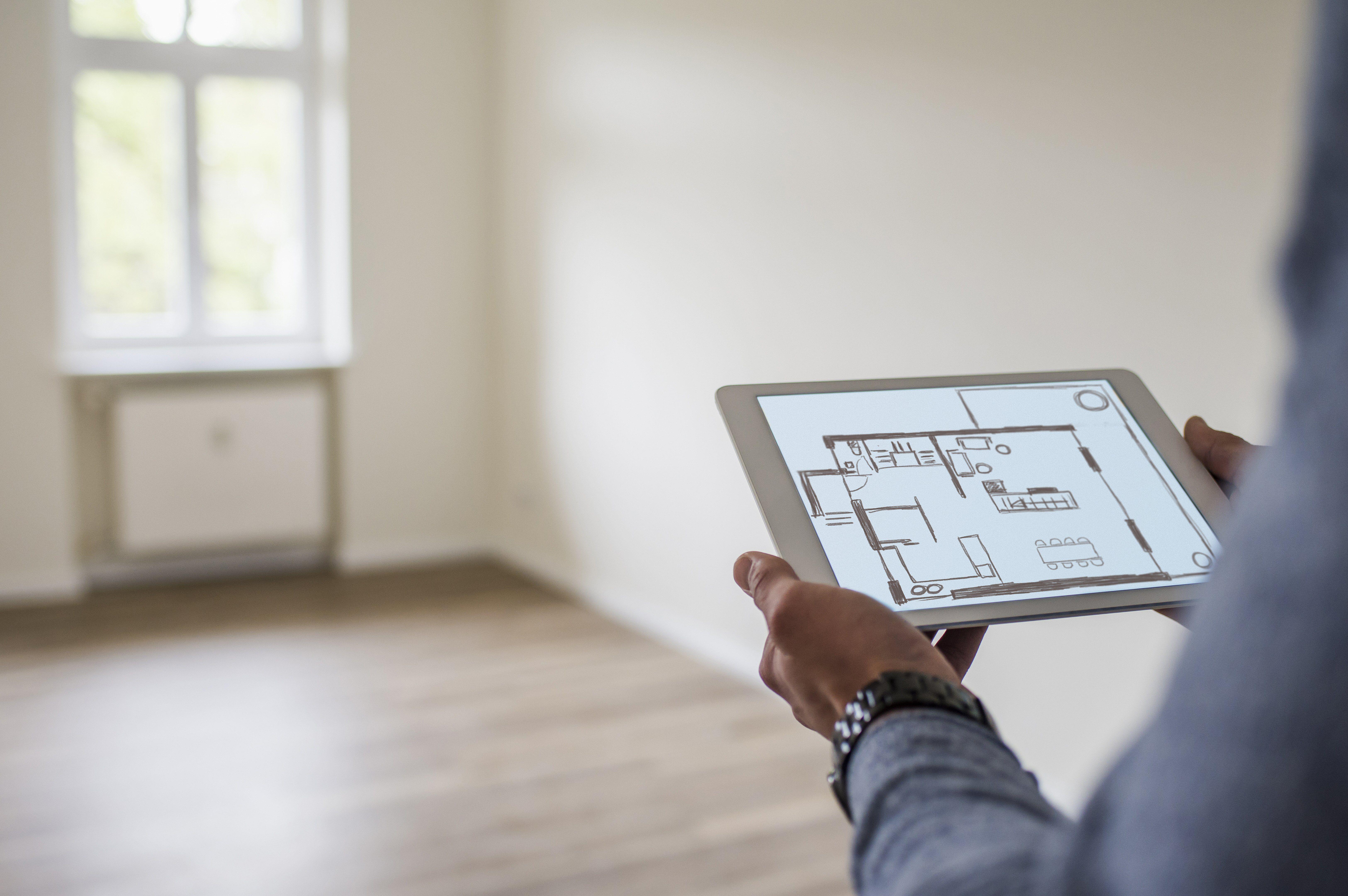 Mann im neuen Haus, das Tablette hält, die einen digitalen Grundriss anzeigt