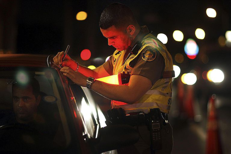 A police offer writes a traffic ticket for a man pulled over during a traffic stop. Many believe that immigrants cause crime.