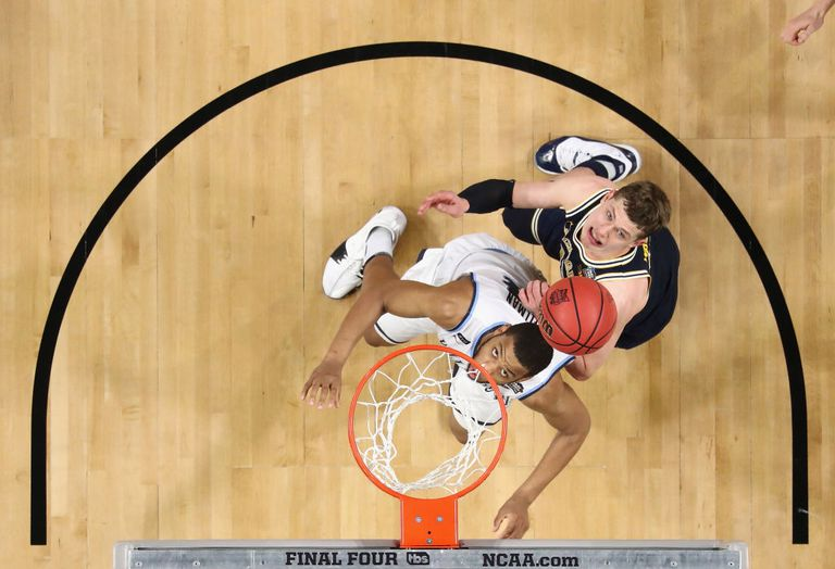 Two basketball players under the hoop