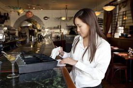 Restaurant employee tallying receipts