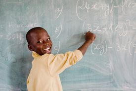 Smiling boy writing on blackboard