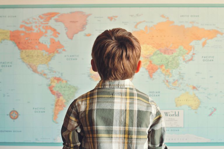 A child looking at a world map.