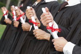 Hands gripping diplomas