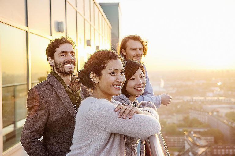 Group of friends overlooking city at sunset.