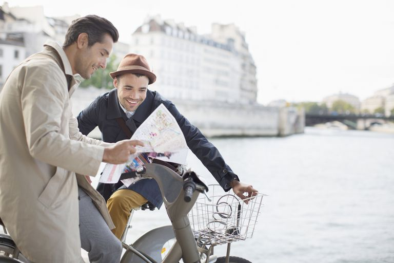 two men looking at map next to river