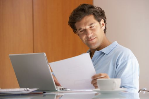 Man holding a sheet of paper with a laptop