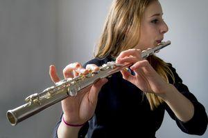 Teenage schoolgirl practises playing her flute.