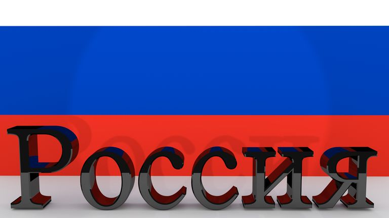 Cyrillic characters made of dark metal meaning Russia in front of a russian flag