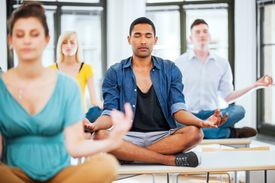 Large group of students meditating on the desks