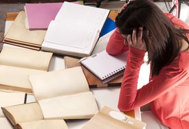 Female student frustrated with the books covering her table