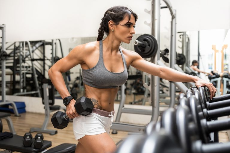 Save to Board Woman holding dumbbell in gym