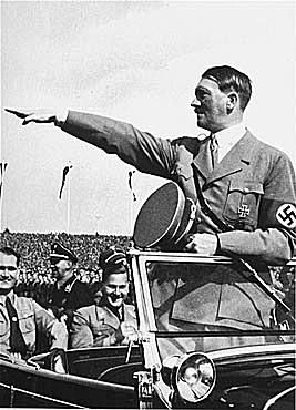 Adolf Hitler salutes the ranks of German youth from his car.