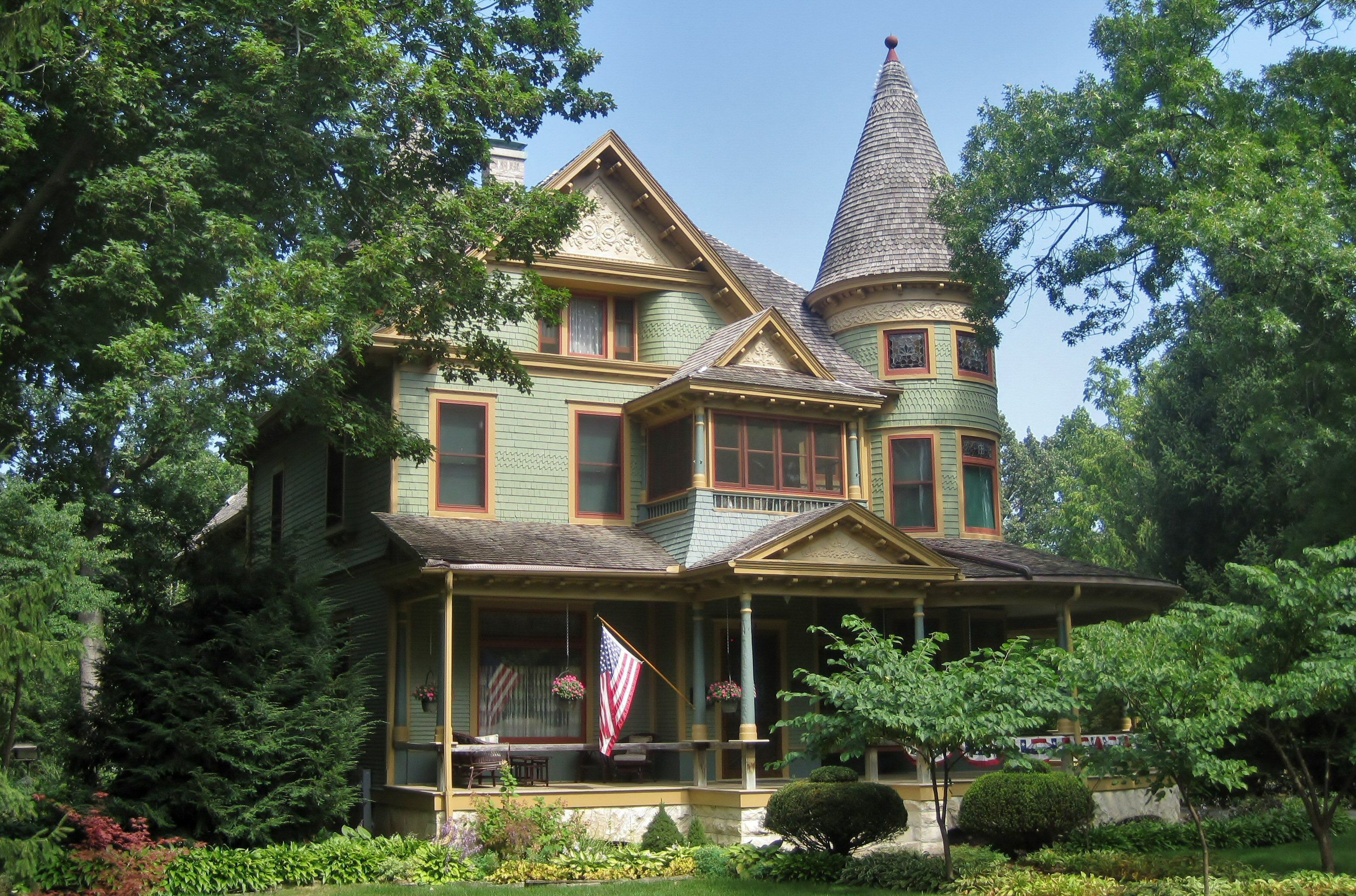 multi-story green sided house with red and yellow trim, front gable, pediments, round tower, front porch