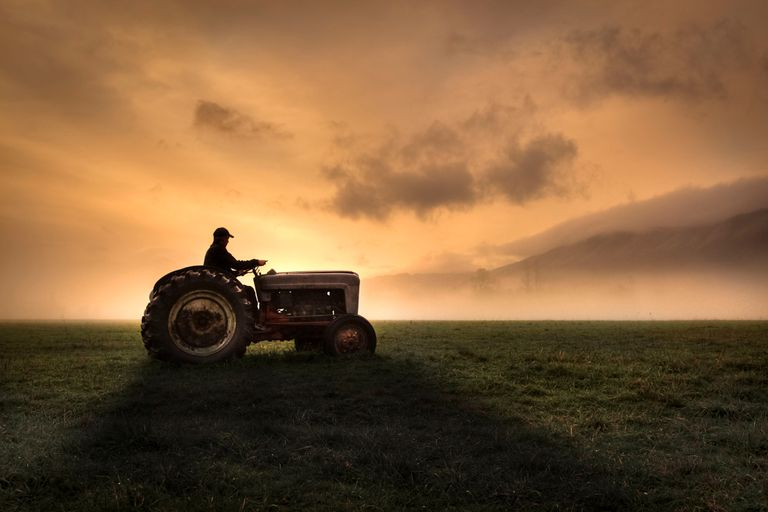 Farmer riding tractor with sunset in background