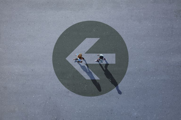 Top view of two people walking across asphalt with big painted arrow