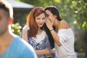 Young woman whispering secret into friend's ear