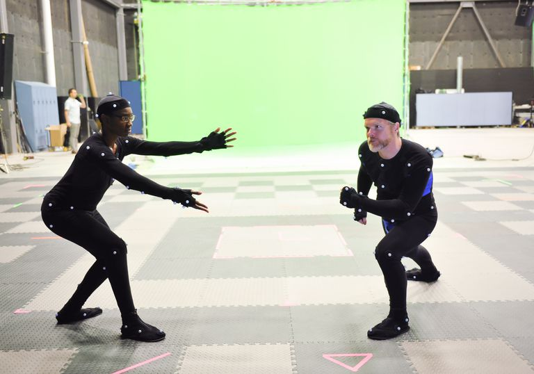 Actors doing motion capture in studio in front of a green screen