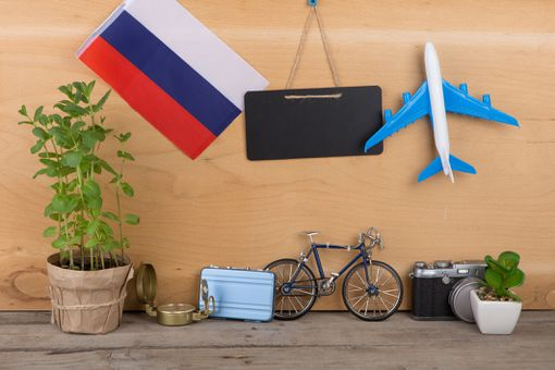 Travel time concept - blank blackboard, flag of the Russia, camera, airplane model, little bicycle and suitcase, compass on wooden background